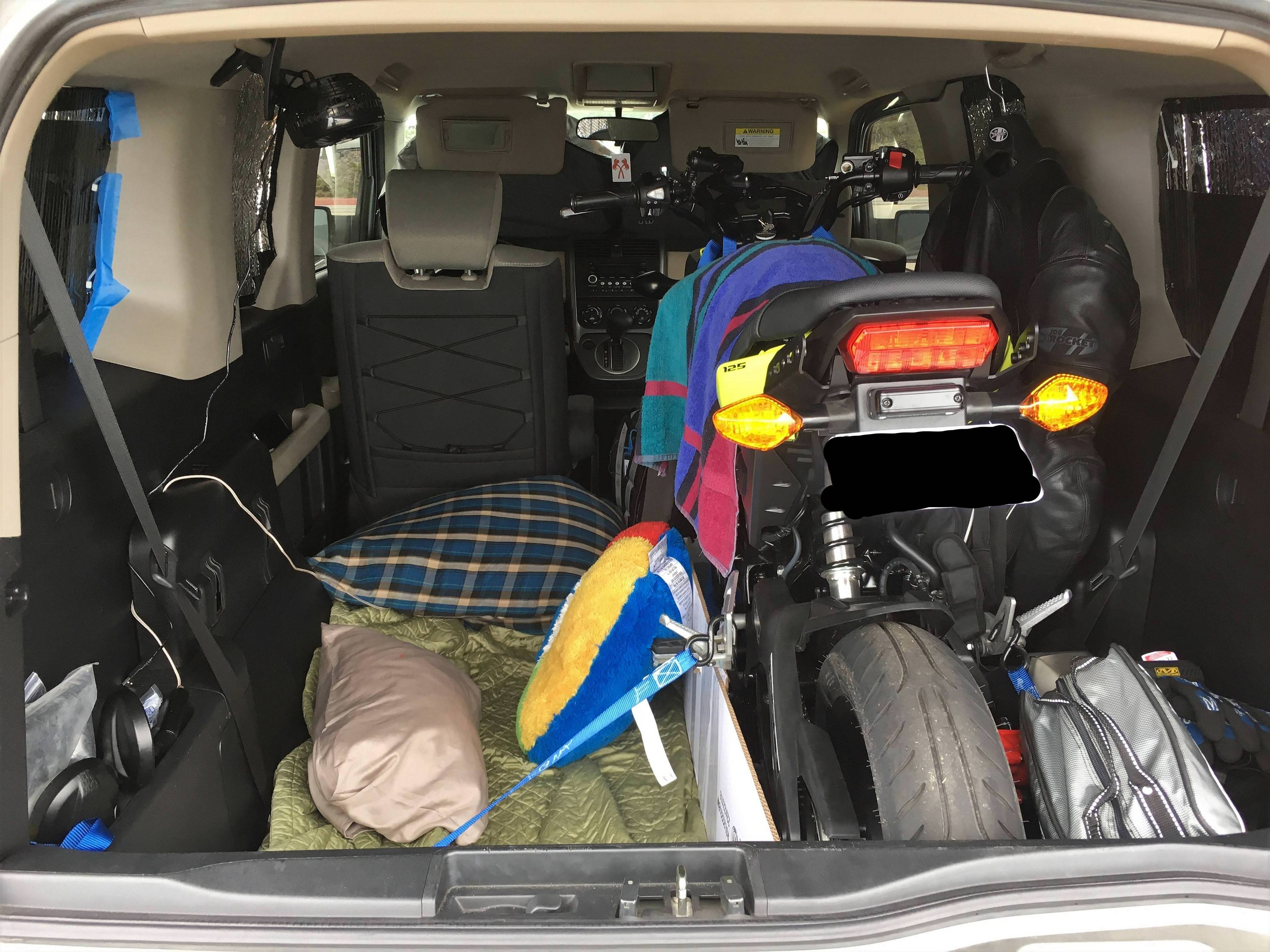 honda element with a honda grom inside and a bed platform