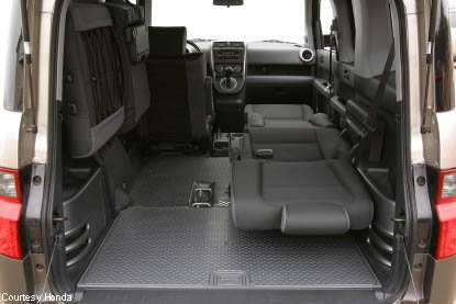 honda element interior configuration both passneger seats folded laying back while backseat drivers side is mounted up against the wall